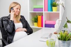 孕妇在办公室谈话在电话 免版税图库摄影