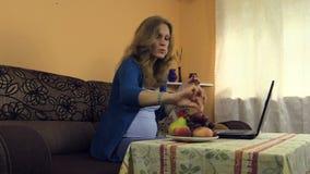 孕妇在家与膝上型计算机,快餐葡萄,果子花瓶一起使用 影视素材