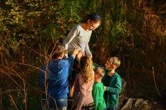 孕妇在树的一个森林里站立,并且四个孩子在公园在她的母亲旁边 许多孩子的母亲与 库存照片