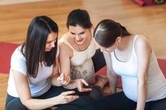 孕妇在电话的健身室观看的图片坐在锻炼以后 免版税库存图片