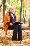 孕妇在秋天公园读了书 图库摄影
