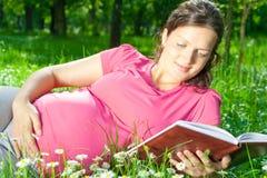 孕妇在草的阅读书 免版税库存照片