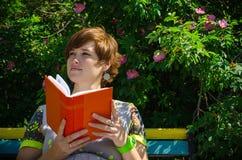 孕妇在长凳的读书笔记本 库存图片