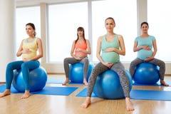 孕妇坐在健身房的锻炼球 免版税库存图片
