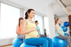 孕妇坐在健身房的锻炼球 库存图片