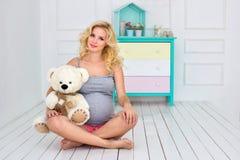 孕妇坐并且拿着玩具熊 免版税图库摄影