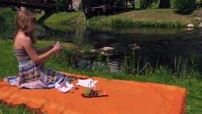 孕妇坐格子花呢披肩在河水附近并且折叠纸船 股票录像