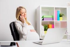 孕妇工作在办公室和谈话在电话 库存图片