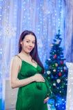孕妇愉快在家在圣诞树附近在庆祝时 库存照片