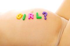 孕妇的腹部有女孩字法的 免版税库存图片