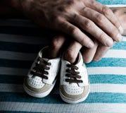 孕妇藏品在她的腹部的童鞋 免版税库存图片