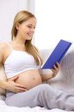 孕妇阅读书在家 免版税库存图片
