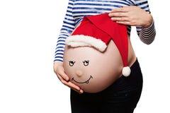 孕妇 与圣诞老人帽子的婴孩爆沸 图库摄影