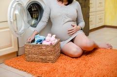 孕妇洗涤婴孩衣裳 免版税库存照片