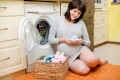 孕妇洗涤婴孩衣裳 免版税库存图片