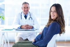 孕妇画象有男性医生的诊所的 免版税库存照片