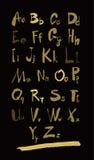 字母表在小写,大写上写字并且编号在黑色的金子 免版税库存图片