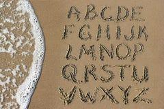 字母表在手写上写字在海滩的沙子 库存照片