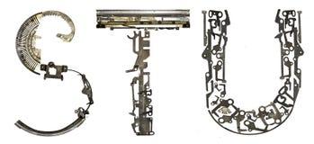 字母表在` S, T,从金属零件装配的U `上写字 免版税库存照片