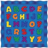 字母表婴孩被子,明亮的圆点信件,蓝色缎边界 免版税库存图片