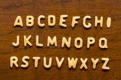 字母表由被隔绝的通心面信件做成在木背景 库存图片