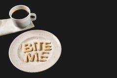 字法侧视图咬住我由曲奇饼面团做了在有咖啡杯的板材 库存图片