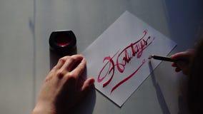 字法和题字假日的过程射击特写镜头在白色纸的在白色台式的在艺术 影视素材