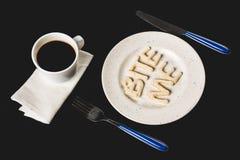 字法顶视图咬住我由曲奇饼面团做了在有咖啡杯的板材 免版税库存照片