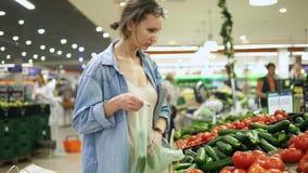 字符逗人喜爱的愉快的小的购物超级市场 偶然的少妇在菜部门 选择新鲜的黄瓜 放他们入 股票录像