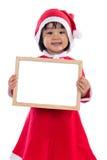 存空白的消息的圣诞老人服装的亚裔中国小女孩 库存照片