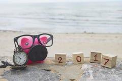 存钱罐和木立方体与2017年在海滩的桌上 库存图片
