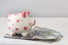 存钱罐和美元在白色桌上 财务 节省额 图库摄影