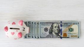 存钱罐和美元在白色桌上 财务 节省额 免版税库存照片