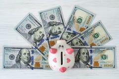 存钱罐和美元在白色桌上 财务 节省额 免版税图库摄影