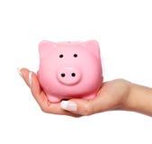 存钱罐在白色隔绝的女性手上。储款 图库摄影