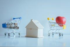 存钱罐家模型选择聚焦和迷离微型购物车,红色心脏模型,硬币堆积,财务和节约金钱概念 库存照片