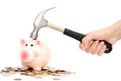 存钱罐由在建议金钱的堆的锤子碰撞了或刹车了金融危机 免版税库存照片