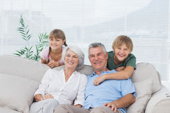 孙和祖父母坐长沙发 库存照片