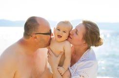 孙和祖父母获得乐趣户外在夏天晴天由海滩 免版税库存图片