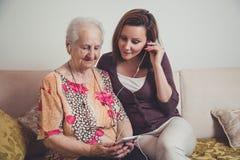 孙女和祖母听的音乐 免版税库存图片