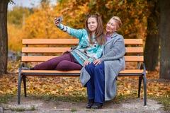 孙女和祖母在秋天公园做在一条长凳的selfie 免版税库存图片