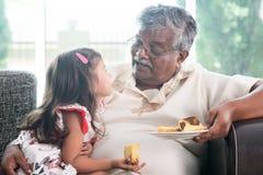 孙女和祖父吃蛋糕 免版税图库摄影