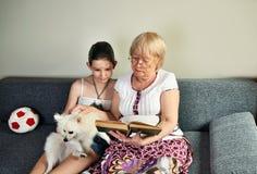 孙女在她的祖母旁边坐长沙发并且读了 库存照片