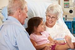 孙女访问的祖母在医院病床上 免版税库存照片