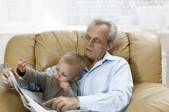 孙子仿效祖父-投入他的玻璃 库存照片