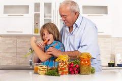孙子和祖父吃健康食物 免版税图库摄影