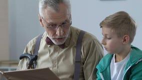 孙子的男性领抚恤金者读书故事书,说明课题,帮助 股票录像
