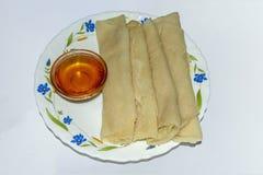 孟加拉人烹调- Patishapta Pitha用在碗的棕榈糖糖浆 免版税库存照片