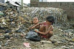 孟加拉国的孩子采取从垃圾填埋的有用的物品 免版税图库摄影