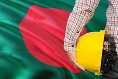 孟加拉国的工程师拿着与挥动孟加拉国旗子背景的黄色安全帽 建筑和大厦概念 免版税库存照片